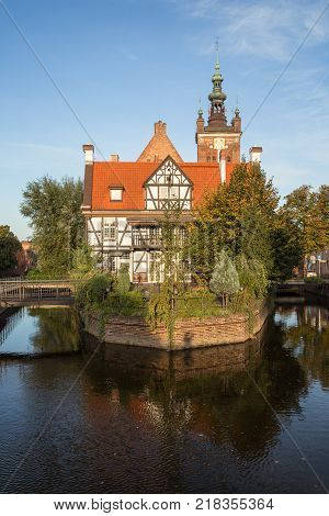 Miller's House (Dom Mlynarza) at the Mill Island on Raduni Canal in Gdansk's Old Town in Poland on a sunny day. It's the old headquarters of the Millers guild. St. Cathrine's Church is in the background.