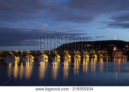 Petrin Hill, lit Charles Bridge (Karluv most) and old buildings at the Mala Strana District (Lesser Town) and their reflections on the Vltava River in Prague, Czech Republic, at dusk. Copy space.