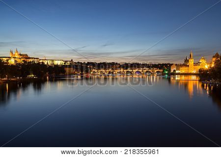 View of the lit Prague (Hradcany) Castle, Charles Bridge (Karluv most), buildings at the Old Town and their reflections on the Vltava River in Prague, Czech Republic, at night.