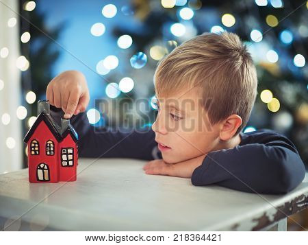 little boy on a Christmas night looking at a small house