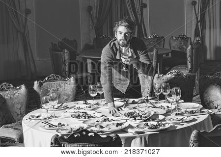 Handsome young man with beard and blond hair eats vegetables with wine in glass from dirty plates with leftovers or residues of food after banquet dinner on table in restaurant