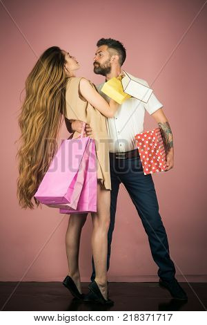 Black Friday happy holiday relations. Shopping and sale. Fashion shopaholic couple. Girl and bearded man hold present pack cyber Monday. Couple in love hold shopping bag near pink wall.