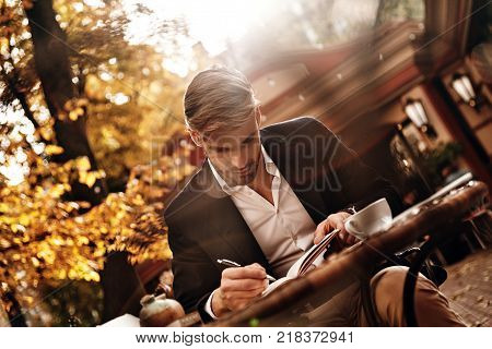 Everything must be planned. Good looking young man in smart casual wear writing something down in his personal organizer while sitting in restaurant outdoors