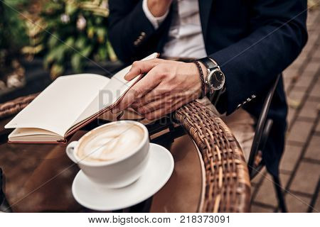Organizing every minute. Close up of young man in smart casual wear keeping his personal organizer open while sitting in restaurant outdoors