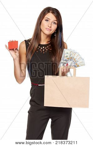 Cash or credit card payment choice. Dubious woman holding paper shopping bag with blank copy space for text and cash US dollars in one hand and blank credit card in other, over white background