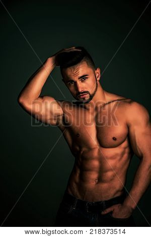 Man with muscular body and bare chest or coach sportsman in jeans on black background sport and workout dieting and fitness