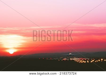 The plane takes off at an airfield on the background of sunset toned