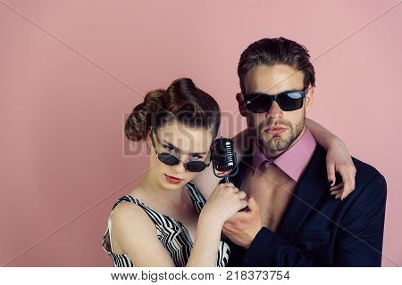 Couple in love in glasses sing in microphone. Singer man and woman with retro hair and makeup. Pinup girl and man on pink background radio. Beauty and vintage fashion music band. Music and love. poster