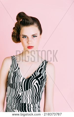 pinup youth and look. Makeup hairdresser and cosmetics. Beauty and fashion cosmetics. Woman with retro hair and fashionable makeup pinup. Girl in stylish vintage dress on pink background.