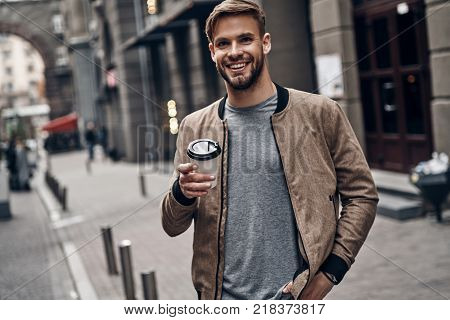 Enjoying coffee outdoors. Handsome young man in casual wear holding disposable cup and smiling while walking through the city street