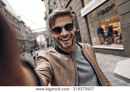 Positively charming. Self portrait of handsome young man in casual wear smiling while standing outdoors