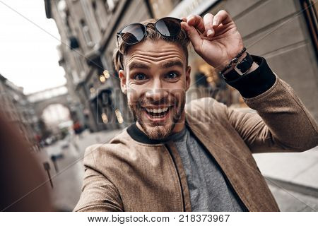 So charming. Self portrait of handsome young man in casual wear smiling and making a face while standing face outdoors