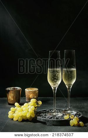 Two glasses of white champagne served on black wooden decorative board with candles and green grapes over dark texture background. Copy space