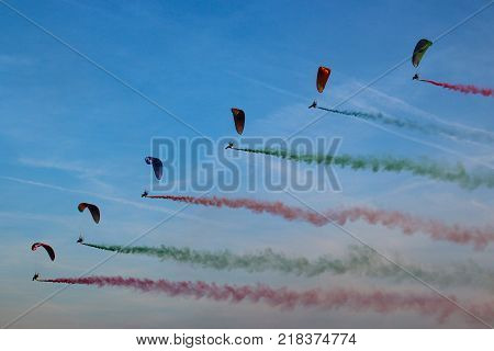 Paragliding with colored smoke behind, on the background of blue sky