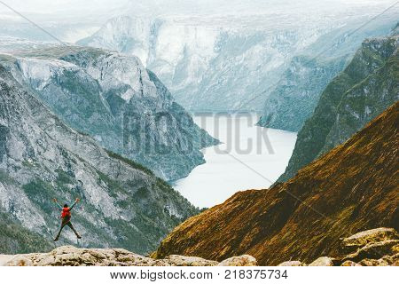 Jumping happy Man in Norway mountains Travel Lifestyle concept adventure active vacations with backpack outdoor hiking Naeroyfjord