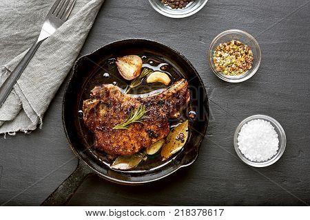 Fried pork steak in frying pan on dark background. Top view flat lay food