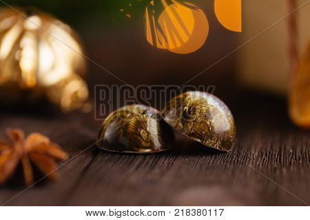 Closeup of luxury handmade bonbons on wooden background with christmas decorations. Exclusive chocolate candies. Holiday product concept for chocolatier