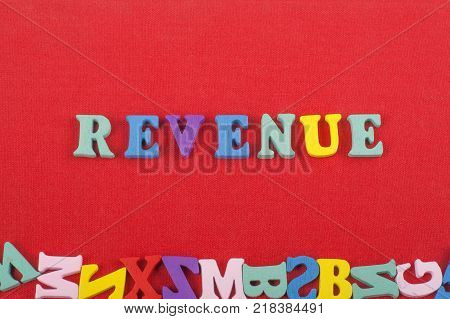 REVENUE word on red background composed from colorful abc alphabet block wooden letters, copy space for ad text. Learning english concept