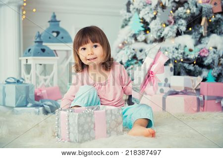 Little baby girl opens New Year gift near Christmas tree.