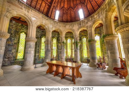 Argyll, Scotland, United Kingdom - June 1, 2015: semi-circular apse with pillars, arches and glass windows. Wooden altar of Saint Conan's Kirk gothic church in Argyll town in Scottish Highlands.