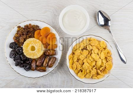 Dried fruits in white plate bowls with sour cream corn flakes and spoon on wooden table. Top view
