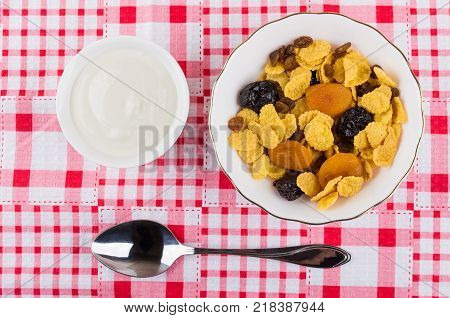 Corn flakes with dried fruits in bowl sour cream and spoon on table. Top view