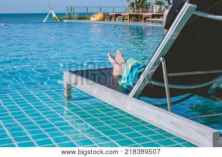 Vacation and Holiday Concept : Woman lying in daybed beside swimming pool at resort. (Selective focus)