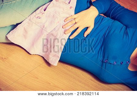 Parenthood waiting for baby concept. Adult woman showing her big pregnant belly lying on wooden floor