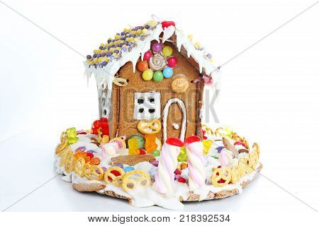Gingerbread candy sugar house. Fairy tail candy house covered with snow and colorful candies Homemade gingerbread house with colorful candy decoration. Christmas ornaments. Cute christmas house. Sweets.