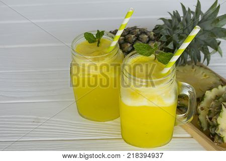 pineapple smoothie and pineapple fruits drink in the morning, healthy on white wood background