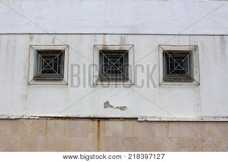 Three wooden frame rectangle glass windows with partially rusted metal bars mounted on dilapidated wall outside