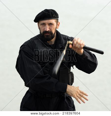 The security man in black uniform and beret is practicing martial arts with nunchaku on white background.
