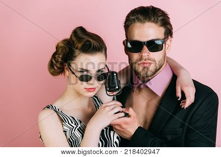 Beauty and vintage fashion music band. Pinup girl and man on pink background radio. Music and love. Singer man and woman with retro hair and makeup. Couple in love in glasses sing in microphone. poster