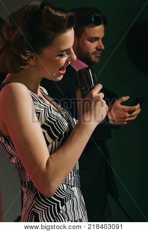 Music and love. Pinup girl and man sing karaoke radio. Couple in love in glasses sing in microphone. Singer man and woman with retro hair and makeup. Beauty and vintage fashion music band.