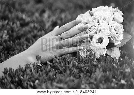 Closeup view of one big round beautiful fresh wedding bouquet of rose flowers pink white and yellow pastel colors lying on green grass sunny day outdoor with female hand horizontal picture