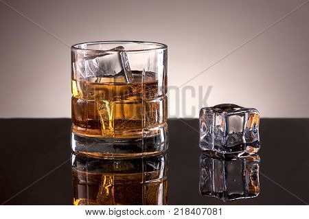 Studio image of liquor. A studio image of a glass filled with ice and liquor.