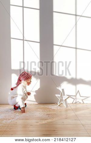 Playful small child wears santa hat, plays with artificial snow in spacious room, looks attentively star, has dreamy and concentrated look. Adorable kid celebrates Christmas holidays indoor.