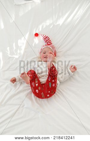 Playful cheerful little girl wears pyjamas and Santa s hat, raises legs, lies on comfortable bed with white bedclothes, enjoys good morning. Funny adorable small child in bedroom. Children and leisure