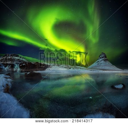 Kirkjufell mountain with beautiful aurora borealis and frozen water falls in winter, Iceland. One of the famous natural heritage in Iceland.
