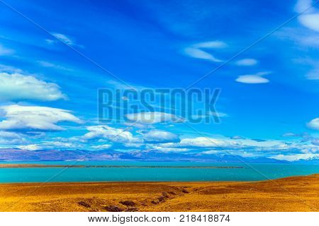 Patagonian Pampas. Flat plain with shallow lakes and yellowed grass. The concept of active and exotic tourism. Summer sunny day in February. Strong wind carries clouds