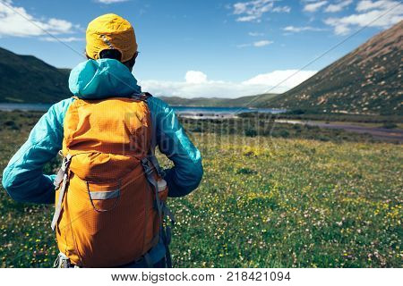young backpacking woman on flowers and grass in high altitude mountains