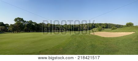 Panoramic view of a golf course featuring greens and sand trap.
