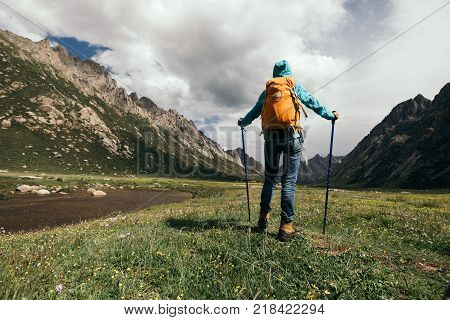 one backpacking woman hiking in the high altitude mountains