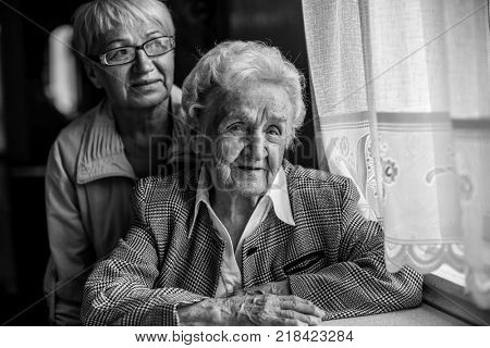 An elderly woman sitting at the table, next to a grown daughter. Black and white photo.