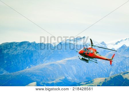 red helicopter flying over the simmental valley in the swiss alps.