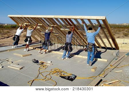Taken in 2008. A group of construction workers raising a wood frame for a house located in Arizona. This was taken with their faces away from the camera because it was impossible to obtain a model release from all of them.