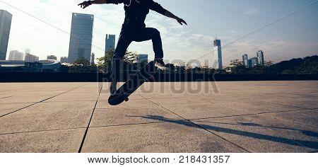 female skateboarder doing a hand on skateboard in city