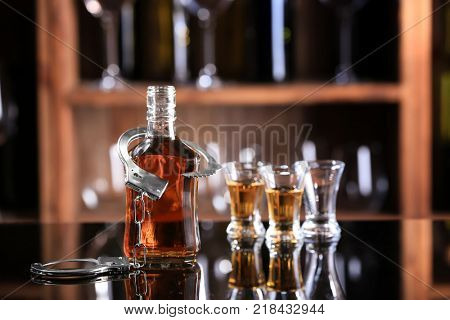 Composition of glassware with handcuffs on table in bar. Alcohol dependence concept