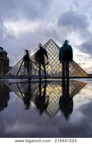 PARIS, FRANCE - DECEMBER 08, 2017: View of famous Louvre Museum with Louvre Pyramid at evening. Louvre Museum is one of the largest and most visited museums worldwide