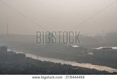 Sunrise on pollution peak day in Wuhan central China with visible dirty haze in the air with view of tortoise mountain and han river